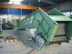 Zielona konstrukcja przenośnika w hali stalowej
