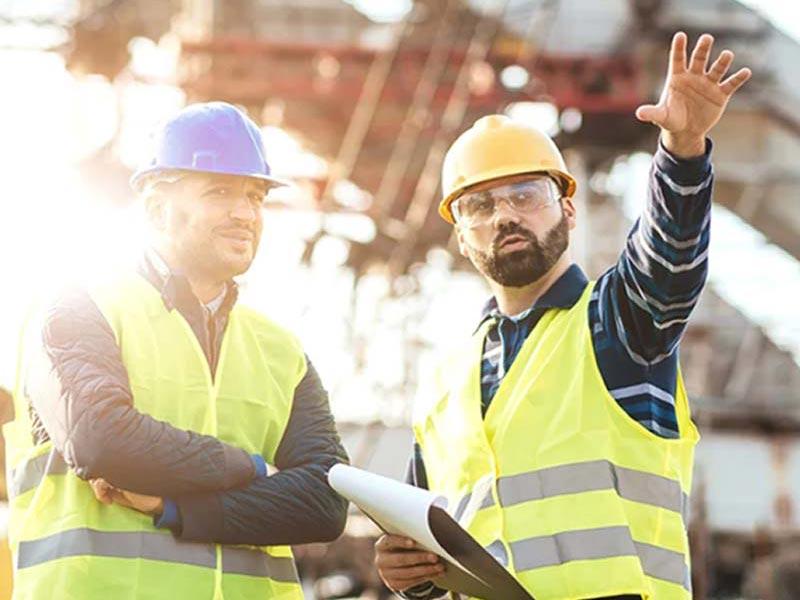Dwóch pracowników budowy rozmawiających o projekcie