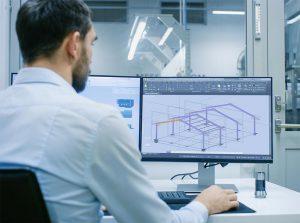 Mężczyzna projektujący halę stalową na komputerze